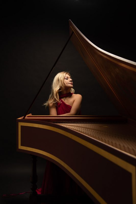 portrait of a lady musician sitting on a piano
